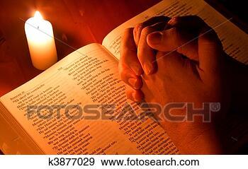 Arquivo Fotográficos - bíblia, vela,  luz, mãos, dobrado,  oração. fotosearch  - busca de fotos,  imagens e clipart