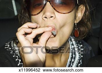 Αποθήκη Φωτογραφίας - γκρο πλαν, νέος,  γυναίκα, γυαλλιά  ηλίου, κάπνισμα,  μαριχουάνα, άρθρωση.  fotosearch - αναζήτηση  φωτογραφιών, εικόνων,  τοιχογραφιών και  clipart