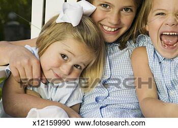 Arquivo de Fotografias - três, irmãs, sentando,  junto, sorrindo,  retrato, close-up.  fotosearch - busca  de fotos, imagens  e clipart