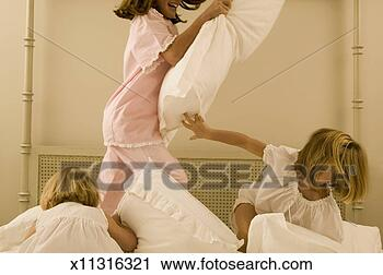 Arquivo de Fotografia - três, irmãs, tendo,  travesseiro, luta,  cama. fotosearch  - busca de fotos,  imagens e clipart