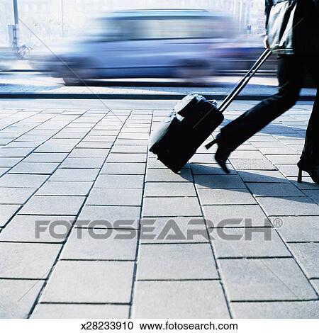 Arquivo de Fotografias - mulher, puxando,  mala, passado,  tráfego, baixo,  seção, (blurred.  fotosearch - busca  de fotos, imagens  e clipart